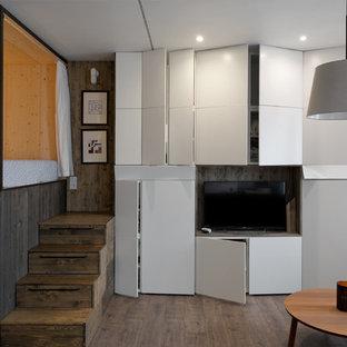 Idee per un piccolo soggiorno minimal stile loft con pareti bianche, pavimento in laminato e TV a parete