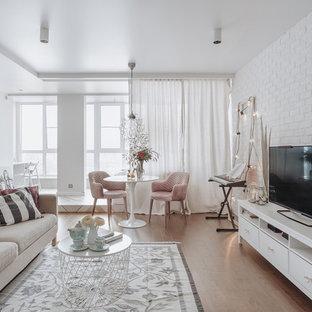 Выдающиеся фото от архитекторов и дизайнеров интерьера: маленькая открытая гостиная комната в скандинавском стиле с белыми стенами, паркетным полом среднего тона, отдельно стоящим ТВ и бежевым полом без камина