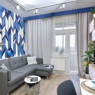 Идея дизайна: изолированная гостиная комната в современном стиле с синими стенами, светлым паркетным полом, отдельно стоящим ТВ и бежевым полом