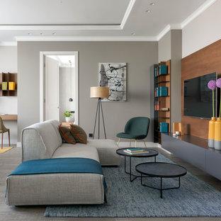 Пример оригинального дизайна: большая открытая, парадная гостиная комната в современном стиле с серыми стенами, паркетным полом среднего тона, серым полом и телевизором на стене