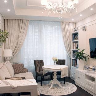 На фото: гостиная комната в современном стиле с бежевыми стенами, телевизором на стене и коричневым полом с