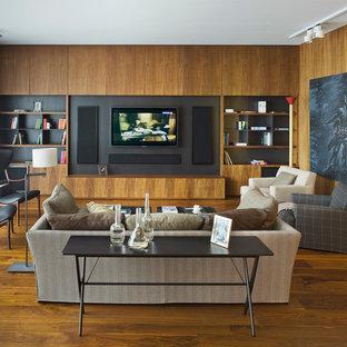 На фото: открытая гостиная комната в современном стиле с коричневыми стенами, паркетным полом среднего тона, мультимедийным центром и коричневым полом без камина с