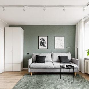 Imagen de salón abierto, actual, pequeño, con paredes verdes, suelo laminado, televisor independiente y suelo marrón