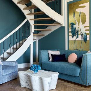 На фото: гостиные комнаты в морском стиле с синими стенами, паркетным полом среднего тона и коричневым полом