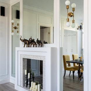 Foto di un grande soggiorno tradizionale aperto con libreria, pareti bianche, pavimento in laminato, camino classico, cornice del camino piastrellata, parete attrezzata e pavimento beige