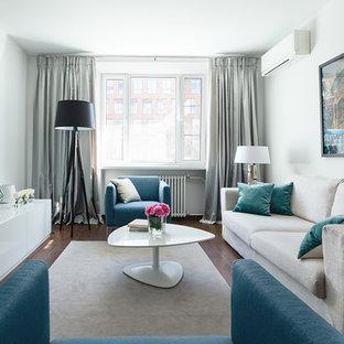 Свежая идея для дизайна: парадная, изолированная гостиная комната в современном стиле с белыми стенами, паркетным полом среднего тона, телевизором на стене и коричневым полом - отличное фото интерьера