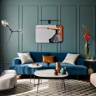 Идея дизайна: гостиная комната в современном стиле с синими стенами, темным паркетным полом, коричневым полом и панелями на части стены