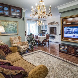 На фото: парадная, открытая гостиная комната среднего размера в викторианском стиле с зелеными стенами, телевизором на стене, темным паркетным полом и коричневым полом без камина с