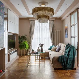 На фото: изолированная гостиная комната среднего размера в стиле современная классика с бежевыми стенами, паркетным полом среднего тона, телевизором на стене и коричневым полом