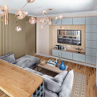 Foto di un soggiorno minimal di medie dimensioni e aperto con sala formale, pareti beige, pavimento in legno massello medio, TV a parete e pavimento giallo