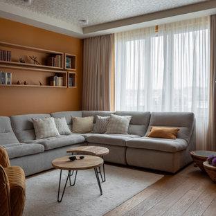 Стильный дизайн: гостиная комната в современном стиле с оранжевыми стенами, паркетным полом среднего тона и коричневым полом - последний тренд