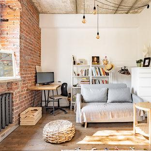 На фото: открытые гостиные комнаты в стиле лофт с белыми стенами и паркетным полом среднего тона без камина