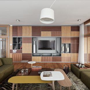 На фото: большая открытая гостиная комната в современном стиле с паркетным полом среднего тона, коричневым полом и телевизором на стене без камина с
