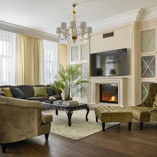 Свежая идея для дизайна: большая открытая, парадная гостиная комната в классическом стиле с бежевыми стенами, темным паркетным полом, стандартным камином, фасадом камина из камня и телевизором на стене - отличное фото интерьера