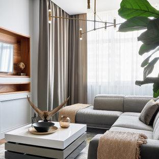 На фото: гостиная комната в современном стиле с серыми стенами и мультимедийным центром без камина с