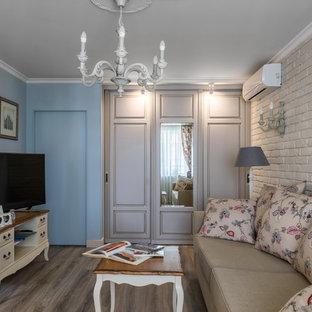 Создайте стильный интерьер: парадная, изолированная гостиная комната в стиле шебби-шик с синими стенами, полом из ламината и отдельно стоящим ТВ без камина - последний тренд