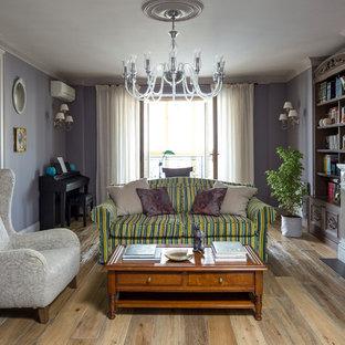 Immagine di un soggiorno tradizionale con sala formale, pareti viola, pavimento in legno massello medio, camino classico e TV a parete