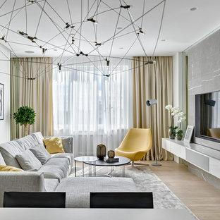 Idée de décoration pour un salon design ouvert avec un mur blanc, un sol en bois clair, un téléviseur fixé au mur et une salle de réception.