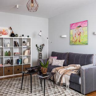 На фото: гостиные комнаты в скандинавском стиле с серыми стенами, паркетным полом среднего тона и коричневым полом