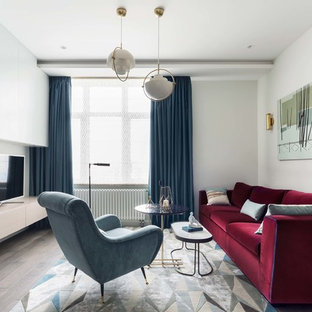 Пример оригинального дизайна: гостиная комната в современном стиле с белыми стенами, темным паркетным полом, отдельно стоящим ТВ и коричневым полом без камина