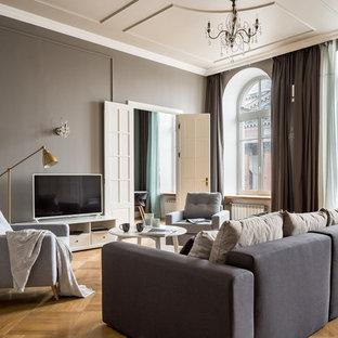 На фото: гостиные комнаты в стиле современная классика с серыми стенами, паркетным полом среднего тона, угловым камином и коричневым полом