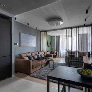 Свежая идея для дизайна: открытая гостиная комната в современном стиле с серыми стенами, светлым паркетным полом, отдельно стоящим ТВ и бежевым полом - отличное фото интерьера