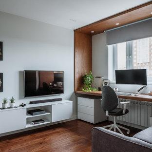 На фото: со средним бюджетом гостиные комнаты в современном стиле с белыми стенами, темным паркетным полом, телевизором на стене и коричневым полом