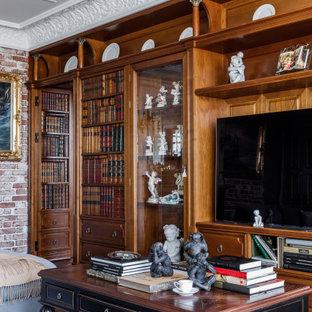 Пример оригинального дизайна: большая изолированная гостиная комната в классическом стиле с библиотекой, зелеными стенами, темным паркетным полом, отдельно стоящим ТВ, коричневым полом и кирпичными стенами