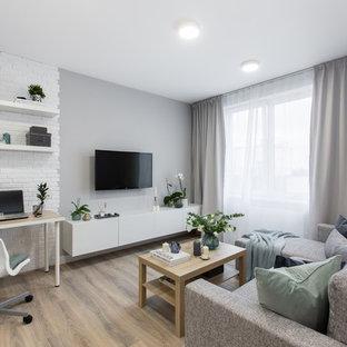 Idéer för att renovera ett litet funkis allrum med öppen planlösning, med grå väggar, laminatgolv, en väggmonterad TV och beiget golv