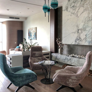Стильный дизайн: открытая гостиная комната в современном стиле с паркетным полом среднего тона и фасадом камина из камня - последний тренд