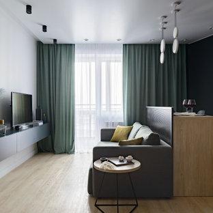 На фото: открытая гостиная комната среднего размера в современном стиле с белыми стенами, полом из ламината, отдельно стоящим ТВ и бежевым полом