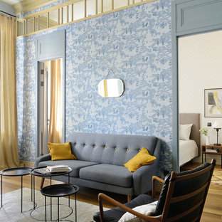Classic formal living room in Moscow with blue walls and light hardwood flooring.
