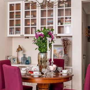 Ejemplo de biblioteca en casa abierta, clásica, de tamaño medio, con paredes beige, suelo de madera en tonos medios, televisor colgado en la pared y suelo marrón