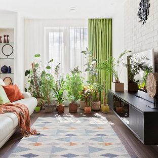 Стильный дизайн: гостиная комната в современном стиле с белыми стенами, темным паркетным полом, коричневым полом и отдельно стоящим ТВ - последний тренд