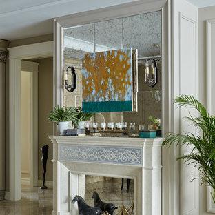 Свежая идея для дизайна: открытая гостиная комната в стиле современная классика с стандартным камином, фасадом камина из камня и бежевым полом - отличное фото интерьера