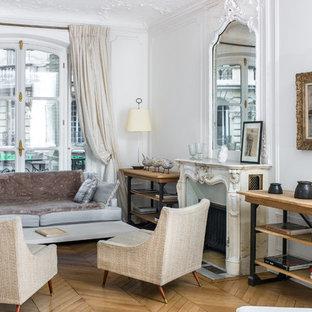 Cette photo montre un salon chic avec un mur blanc, un sol en bois brun, une cheminée standard, un manteau de cheminée en pierre, un sol marron et une salle de réception.