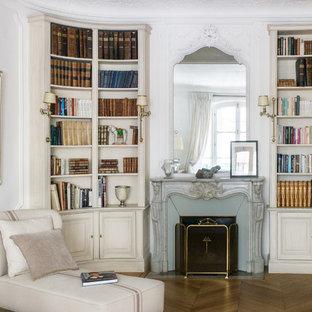 Inspiration pour un salon avec une bibliothèque ou un coin lecture traditionnel avec un mur blanc, un sol en bois brun, une cheminée standard, un sol beige et un manteau de cheminée en pierre.