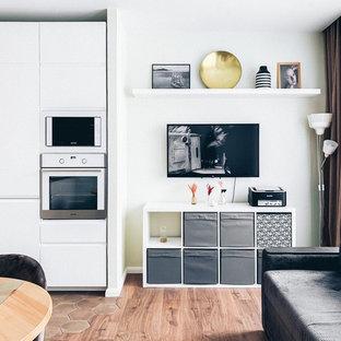 Foto de salón escandinavo, pequeño, con suelo laminado, televisor colgado en la pared y suelo marrón