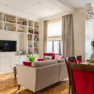 Ejemplo de biblioteca en casa abierta, clásica renovada, de tamaño medio, con paredes beige, suelo de madera en tonos medios, chimenea tradicional, marco de chimenea de madera, televisor independiente y suelo amarillo