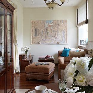 На фото: гостиная комната в классическом стиле с желтыми стенами, темным паркетным полом и коричневым полом с