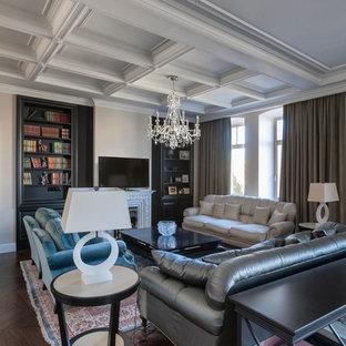 На фото: парадная гостиная комната в классическом стиле с белыми стенами, темным паркетным полом, отдельно стоящим ТВ и коричневым полом с