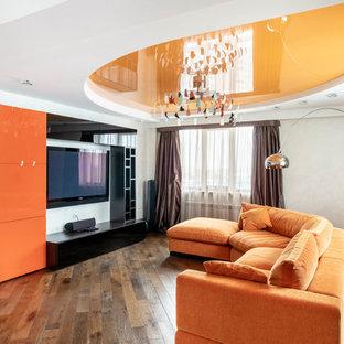 Пример оригинального дизайна интерьера: изолированная гостиная комната в современном стиле с белыми стенами, паркетным полом среднего тона, телевизором на стене и коричневым полом