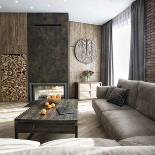 Свежая идея для дизайна: гостиная комната в современном стиле с коричневыми стенами, двусторонним камином, телевизором на стене, светлым паркетным полом и бежевым полом - отличное фото интерьера
