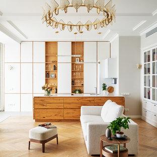 Стильный дизайн: открытая гостиная комната в современном стиле с серыми стенами, паркетным полом среднего тона, телевизором на стене и коричневым полом - последний тренд