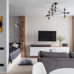 На фото: маленькая открытая гостиная комната в современном стиле с белыми стенами, телевизором на стене и бежевым полом с