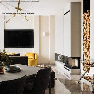 На фото: открытая, парадная гостиная комната среднего размера в современном стиле с бежевыми стенами, полом из керамогранита, камином, фасадом камина из штукатурки, телевизором на стене и серым полом с