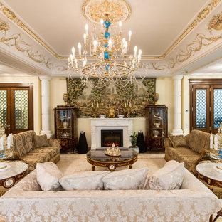 Foto di un soggiorno vittoriano aperto con pareti beige e camino classico