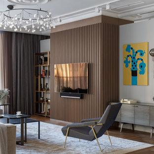 На фото: гостиная комната в стиле модернизм с белыми стенами, паркетным полом среднего тона, телевизором на стене и коричневым полом