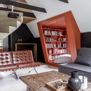 Стильный дизайн: гостиная комната в стиле лофт с с книжными шкафами и полками, черными стенами, светлым паркетным полом и белым полом - последний тренд