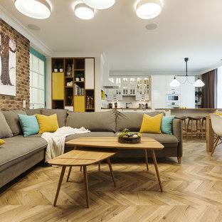 На фото: открытая гостиная комната в скандинавском стиле с бежевыми стенами, полом из ламината и бежевым полом с